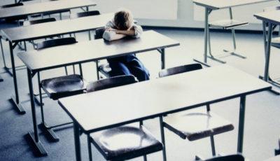 imagen de un niño con la cabeza entre los brazos sentado solo en una mesa de una clase