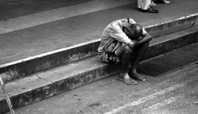 Imagen de un inmigrante de color sentado en la calle