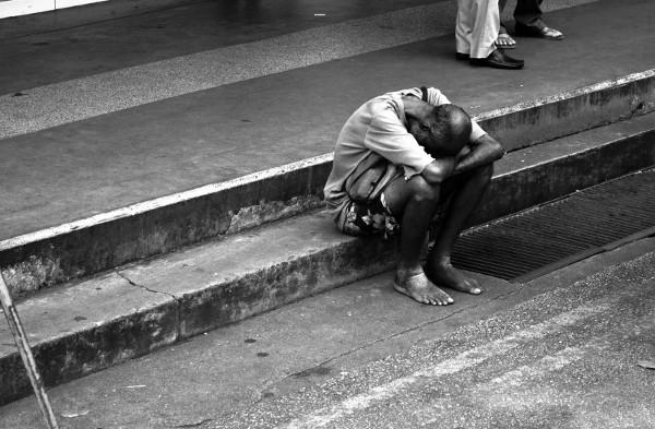 Imagen de un inmigrante de color descalzo sentado en la calle