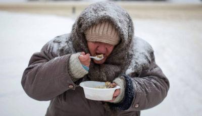una persona que vive en la calle muy abrigada comiendo de un plato de plástico