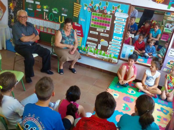 imagen de una pareja mayor en una clase rodeados de niños y niñas