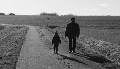 Imagen de un anciano y un niño andando por un camino de tierra