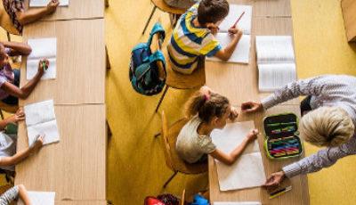 Imagen desde arriba de una clase con suelo y mesas de madera