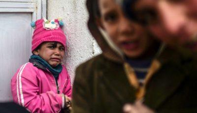 Una niña llora apoyada contra una pared