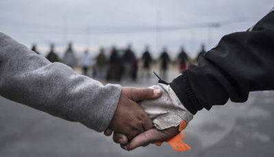 imagen de las manos de dos jóvenes entrelazadas delante en una cadena humana
