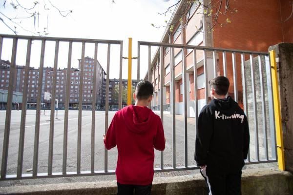 imagen de dos jóvenes ante el patio vacío de un instituto