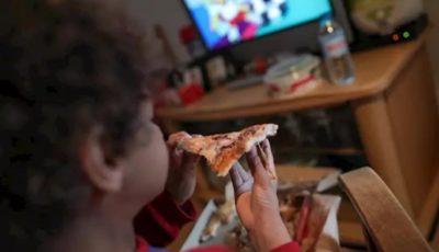 Niño/a come un trozo de pizza delante de la televisión