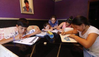 Imagen de una mujer con sus cuatro hijos escribiendo
