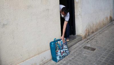 una persona recoge una bolsa de alimentos de su puerta