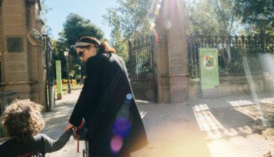 una madre con un niño de la mano entrando a un parque
