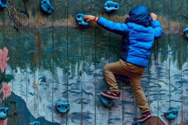 un niño escala en un muro