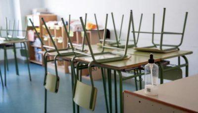 imagen de una mesa de colegio y un bote de gel hidroalcohólico