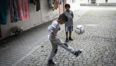 dos niños romaníes juegan al balón