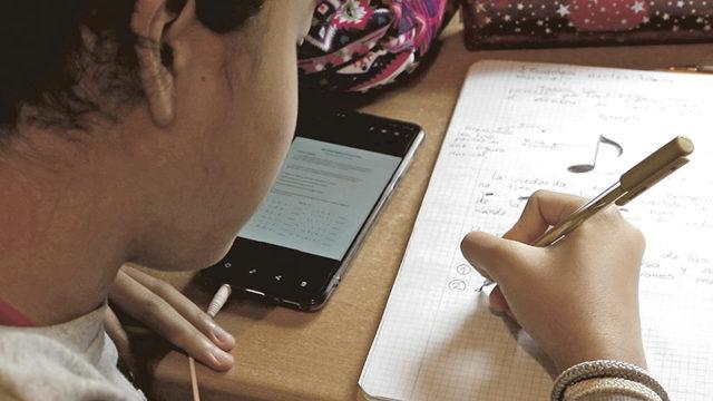 un niño con un smartphone escribe en un cuaderno