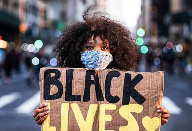 Una mujer con una pancarta en la que pone Blacklives