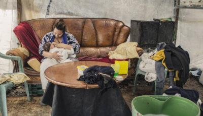 Imagen de una temporera amamantando a un bebé en una chabola en Huelva