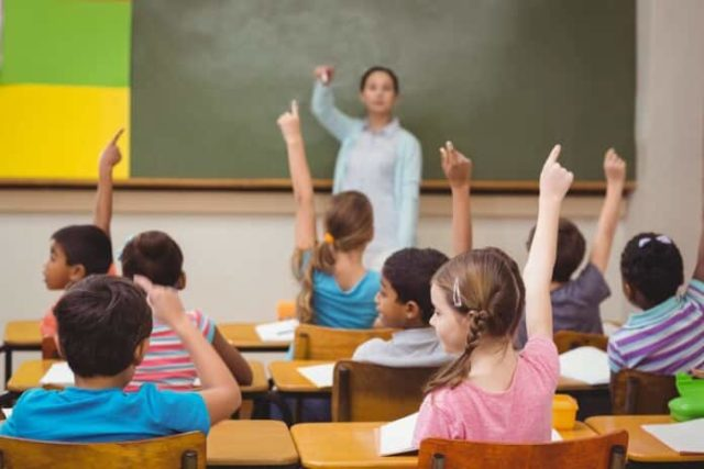 una clase con las manos levantadas