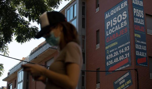 una joven con mascarilla pasa delante de un cartel de alquileres