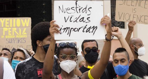 Imagen de una manifestación en la que una joven de color lleva una pancarta con nuestras vidas importan