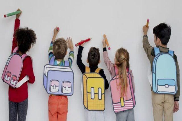 varios niños y niñas dibujando con grandes lápices en una pizarra