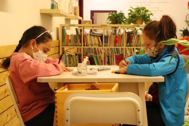 Dos niñas en una mesa de una clase con mascarillas