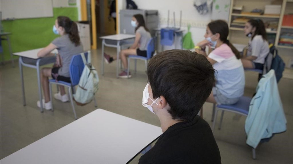 un grupo de niños y niñas asiste a clase con mascarilla