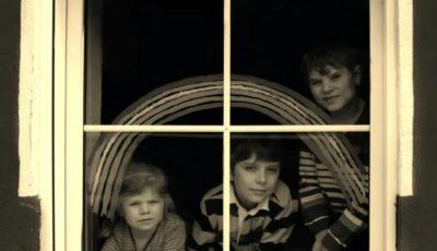 tres niños en una ventana