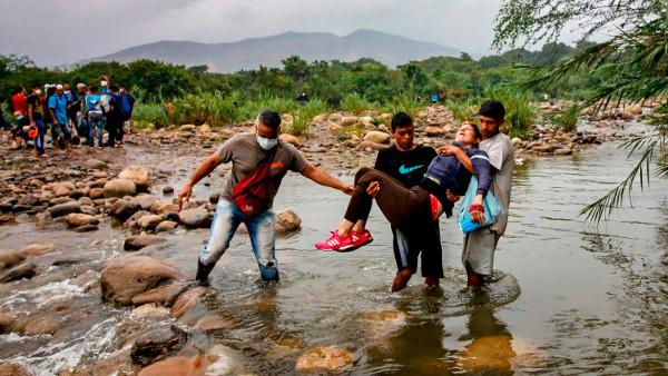 Venezolanos llevan a una mujer hacia la frontera colombiana