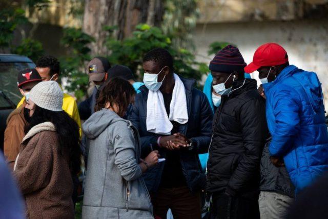 un grupo de inmigrantes hablan con una mujer que toma notas