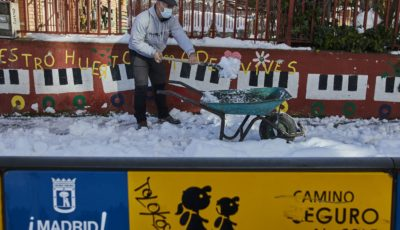 un hombre quita nieve con una pala en un colegio de Madrid