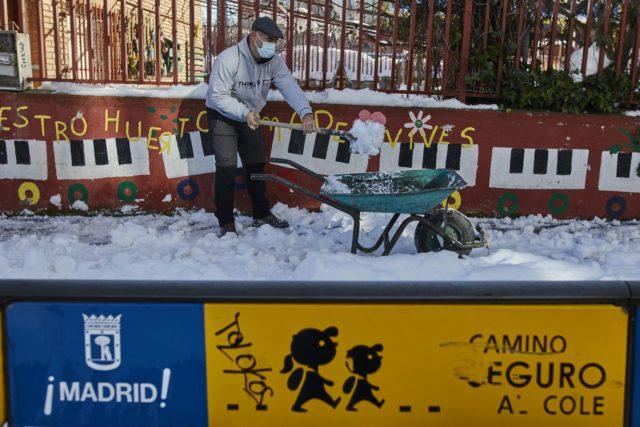 Un hombre quita nieve en un colegio de Madrid