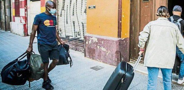 Un hombre de color con mascarilla y maletas