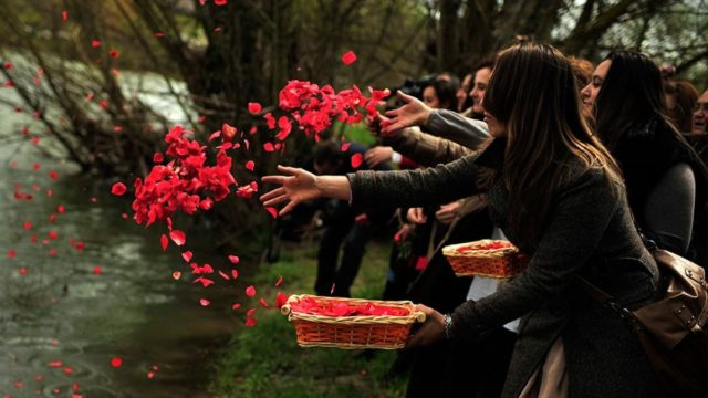 varias jóvenes lanzan pétalos de flores a un río
