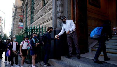 una persona toma la temperatura a la entrada de un colegio en Buenos Aires