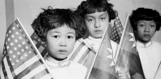 foto antigua de niñas asiáticas con banderas de EEUU