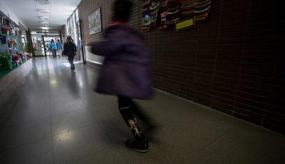 un alumno/a corre por el pasillo de un colegio