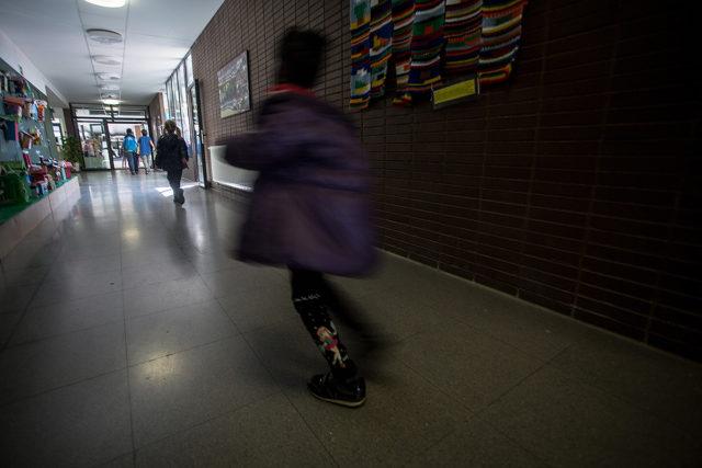 una niña corre por el pasillo de un colegio