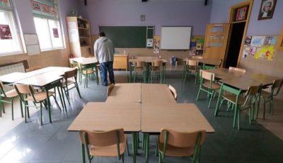 una persona limpia las mesas de una clase