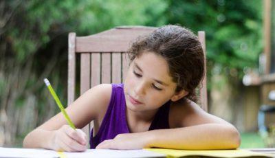 una niña escribe en una mesa al aire libre