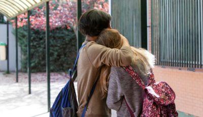 dos jóvenes con mochila se abrazan