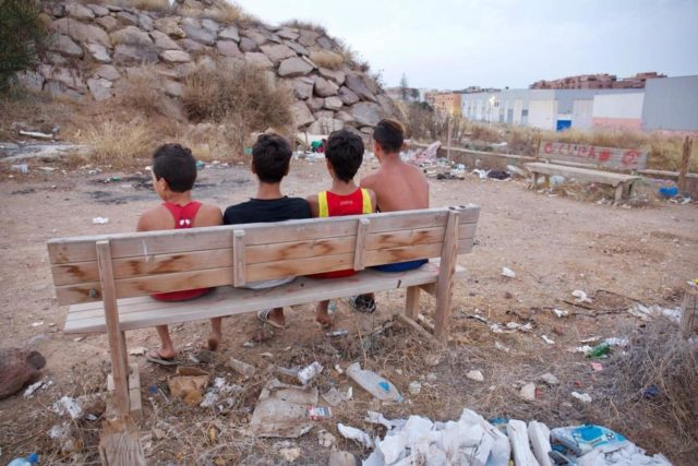 jóvenes inmigrantes sentados en un banco