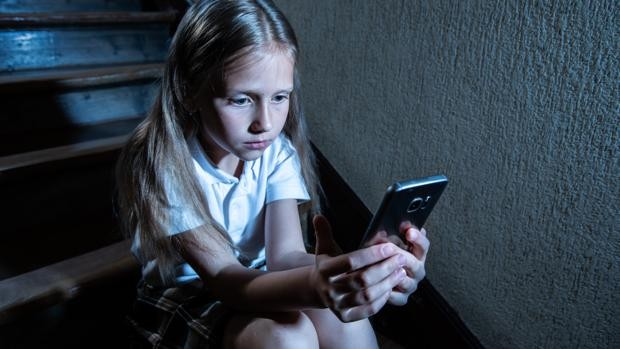 una niña mira un smartphone