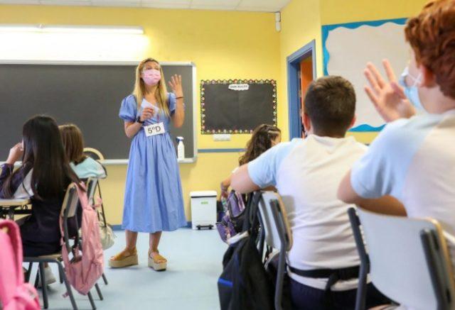 una profesora con mascarilla en una clase