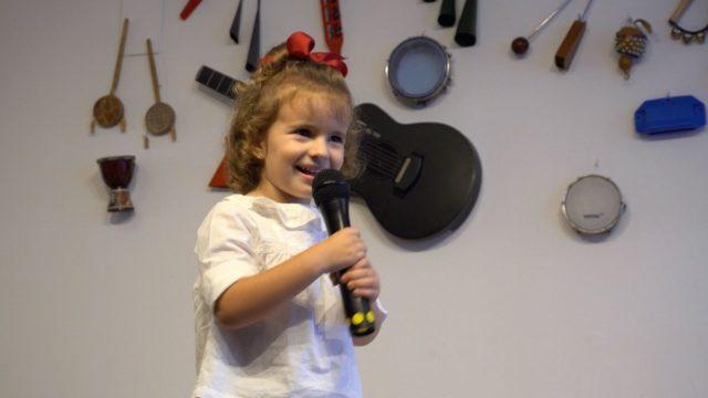 una niña canta con un micrófono