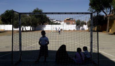varios niños con mascarilla en un campo de fútbol escolar