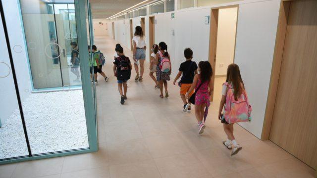 une profesora acompaña a varios alumnos por un pasillo